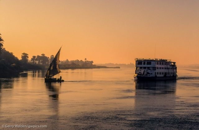 A dhow loaded with passengers and a more modern ferryboat cross the Nile between Aswan and Luxor in the early morning sunlight.