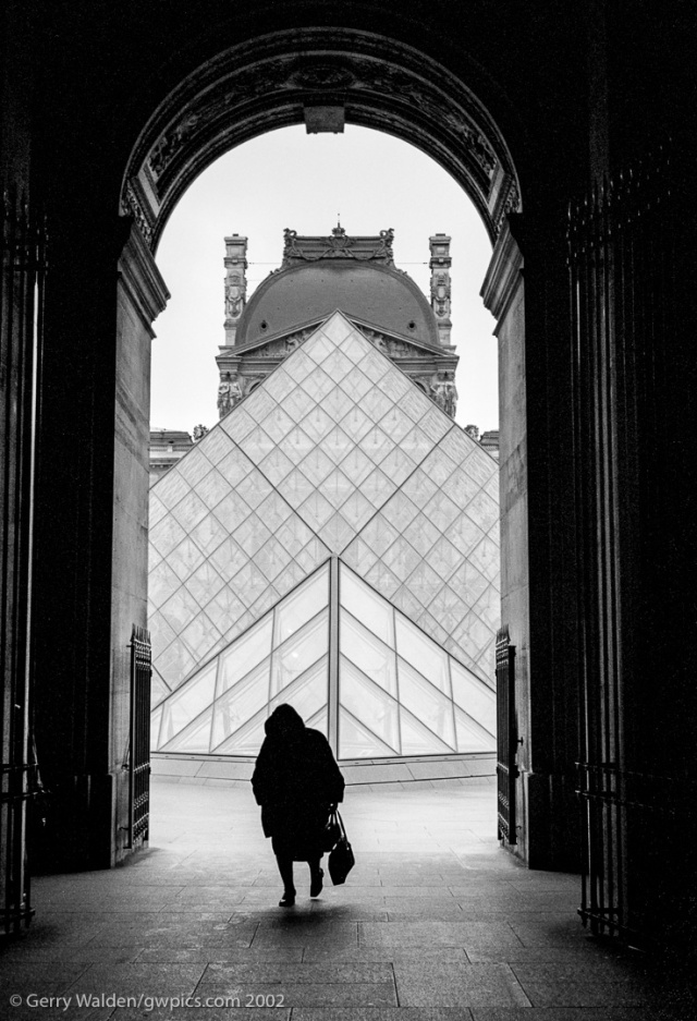 An hooded elderly woman walks through an archway at the Louvre in Paris, France.