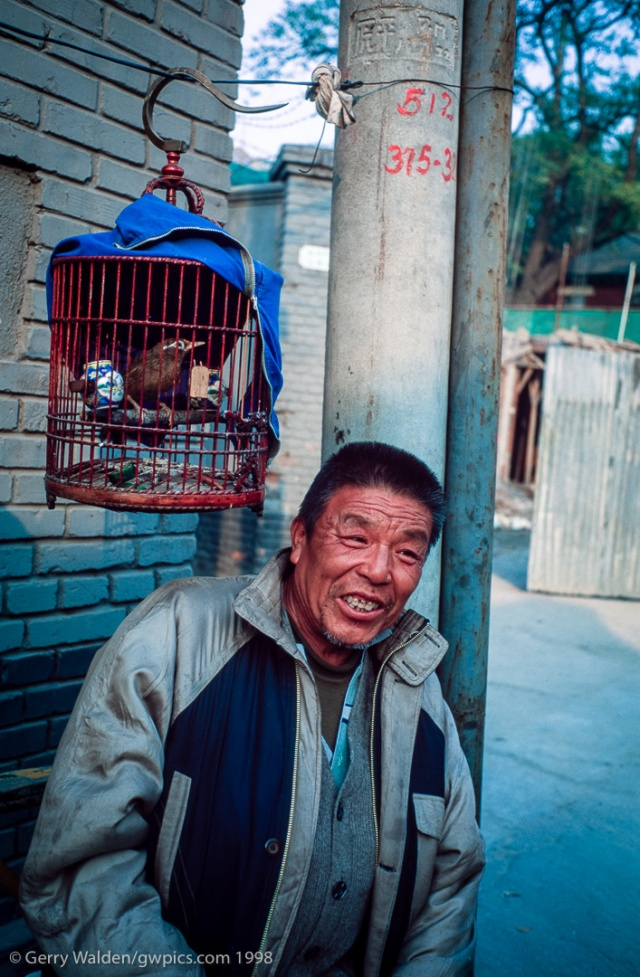 A man sits with a caged bird in a backstreet in the hutongs of Beijing, China.