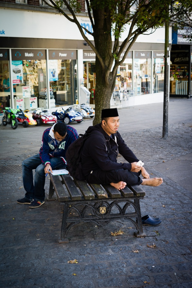 An Asian man sits with his legs crossed and his shoes off to rest his feet (Southampton, England)