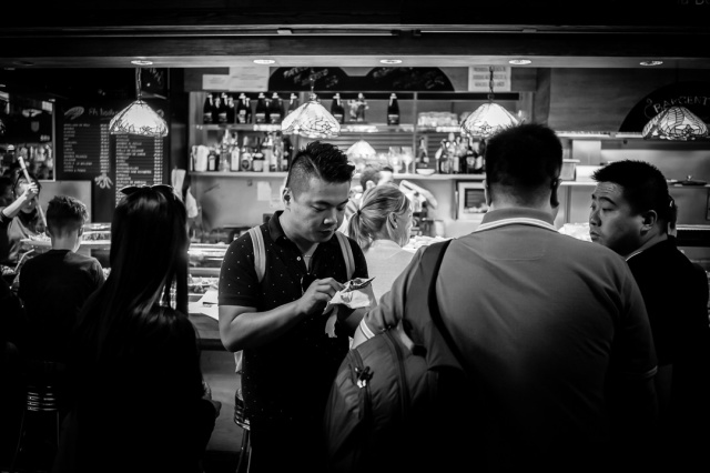 An Asian tourist samples the food in the Boqueria market in the centre of Barcelona, Spain whilst his friends look on.