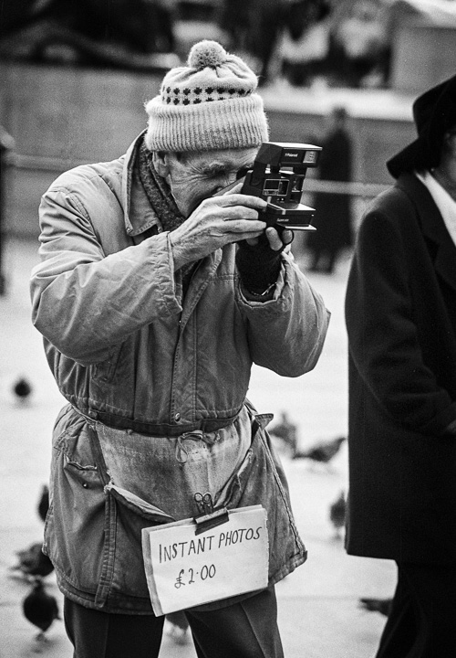 Street photographer in Trafalgar Square, London using a Polaroid camera to take instant photos of tourists in 1993.