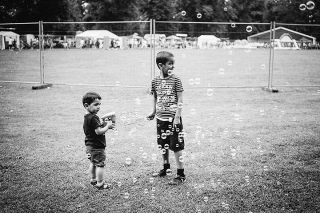 Two young south Asian boys play with a bubble machine at the Mela festivities in Southampton, England