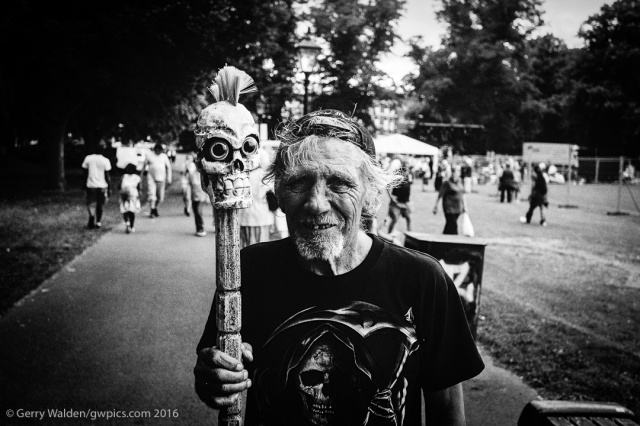 A man walks through the Mela in Southampton holding a carved stick topped by a skull figurine.