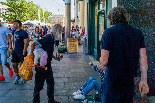 A man carrying a toy horse with a pink tail asks directions from drinkers sat on the pavement in the central precinct of Southampton. They appear to know each other.
