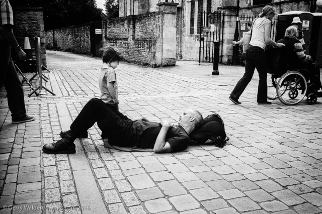 A small boy looks disgruntled at his father who appears to be asleep on the pavement (taken in Romsey, England).
