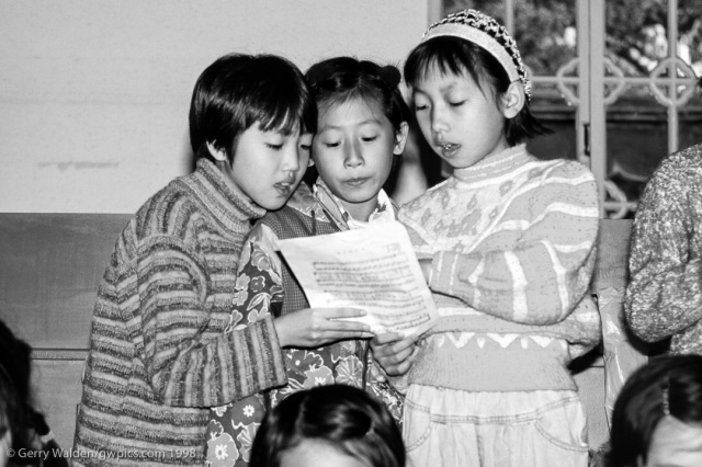 Small children sing a patriotic song for tourists during a school visit in Beijing, China.