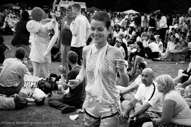 A young girl, hair cust short and studs in her lips, dances with the music from the bamd at the Mela in Southampton, England.