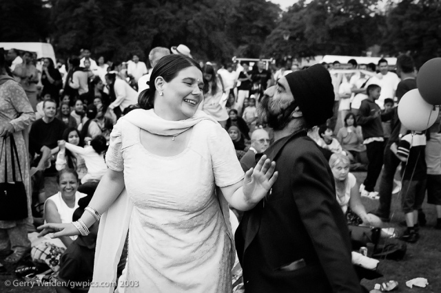 A sikh couple continue to dance seductively together at the Mela in Southampton, England.