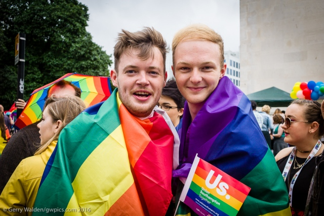 A young male couple decked in Pride flags pose for a photograph at the Southampton Pride event, held in the city for the first time in more than a decade.