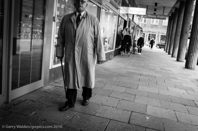 A elderly man in an overcoat and with a cane walks through the streets of Hamburg, Germany.