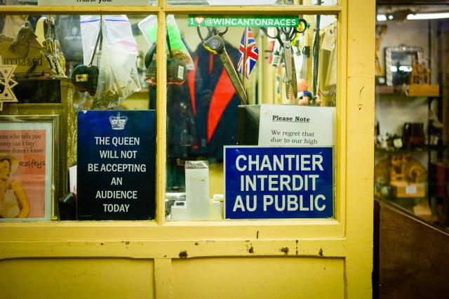 Inside an antiques store in Bath, Somerset, various signs adorn the windows of the office area. The great variety show humour and and information at the same time, making it a friendly place to visit.