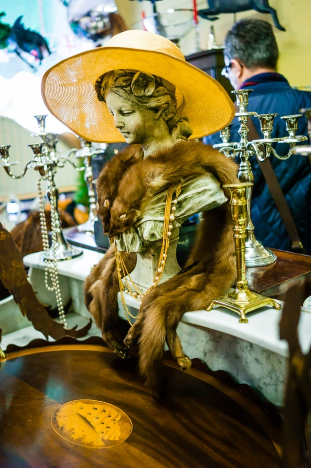Animal pelts and a yellow hat adorn an artistic bust inside an antique shop in Bath, Somerset.