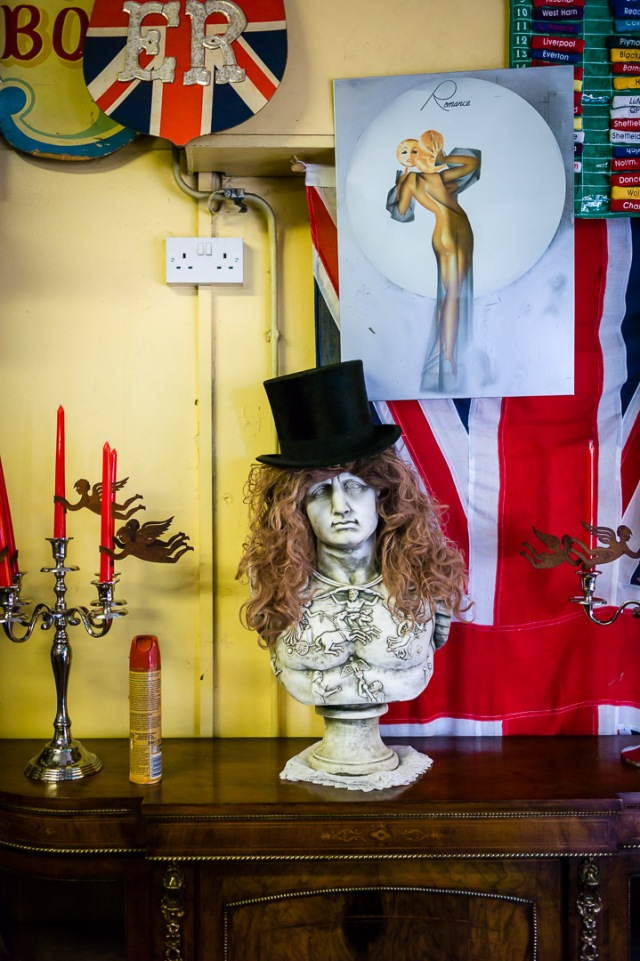 A top hat adorns an artistic bust and the walls display Union Jack and a patriotic sign inside an antique shop in Bath, Somerset.