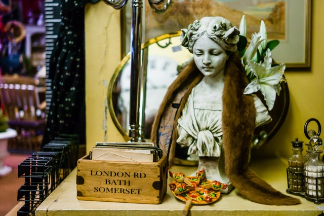 A marble bust is surrounded by other bric-a-brac inside an antique shop in Bath, Somerset.