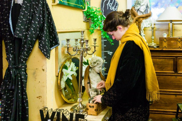 A young woman looks through historic photographs surrounded by other bric-a-brac inside an antique shop in Bath, Somerset.